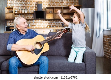 Active movements. Cheerful aged man playing the guitar while his granddaughter having fun on the couch