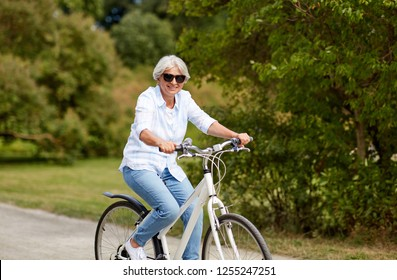 active old age, people and lifestyle concept - happy senior woman riding fixie bicycle at summer park