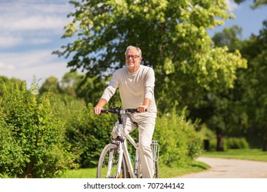 active old age, people and lifestyle concept - happy senior man riding fixie bicycle at summer park