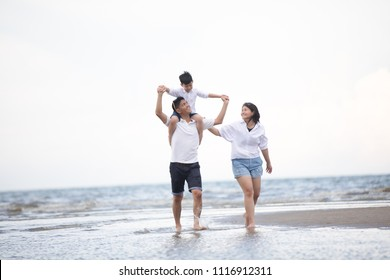 Active parents and people outdoor activity on summer vacations and holiday with children.Happy family and son walk with fun of sunset sea on sand beach.