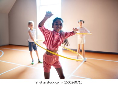 Active PE lesson. Cheerful curly girl enjoying active PE lesson while rolling hula-hoop