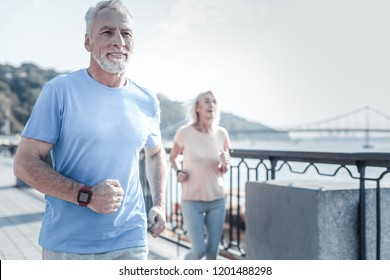 Active pensioners. Delighted bearded male outrunning his wife, keeping smile on his face and looking forward