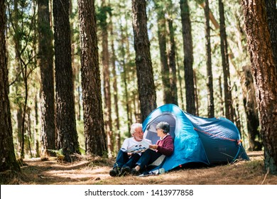 Active people old aged caucasian senior couple travel with camping tent - sit down in the forest having fun together - relationship forever concept for traveler wanderlust retired man and woman