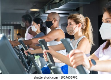 Active people in protective masks having running elliptical trainer class in health club