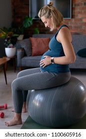 Active pregnancy, healthy fitness expecting woman sitting on exercise ball smiling at kicking baby in tummy