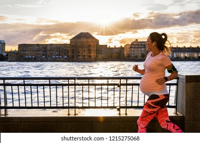 Active pregnant woman running outside in a city at the riverside during sunset