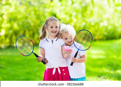 Active preschool girl and boy playing badminton in outdoor court in summer. Kids play tennis. School sports for children. Racquet and shuttlecock sport for child athlete. Kid with racket and shuttle