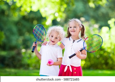 Active preschool girl and boy playing badminton in outdoor court in summer. Kids play tennis. School sports for children. Racquet and shuttlecock sport for child athlete. Kid with racket and shuttle.