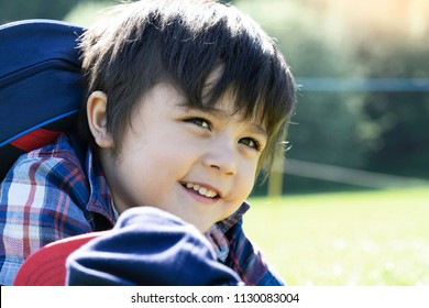 Active preschool kid laying on grass in the hot sunny day, Kid having fun outdoors adventure with school trip, Out door Activities for children, School camp concept