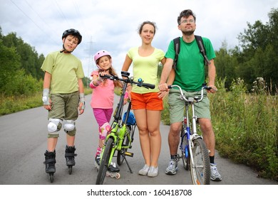 Active rest on nature of the family of four with roller skates and a bicycles
