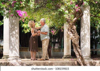Active retired people having fun, happy old man and woman dancing latin american dance in patio