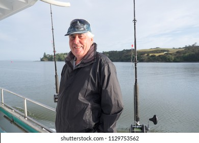 Active retirement - portrait of a retired senior male tourist on a fishing charter boat at Mangonui, Far North District, Northland, New Zealand, NZ