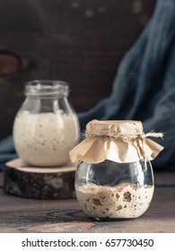 Active rye and wheat sourdough starter in glass jar on brown wooden background. Starter for sourdough bread. Toned image. Copy space. Vertical