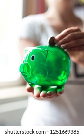 Active save. Woman throwing money in a green piggy Bank. Portrait