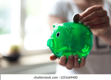 Active save. Woman throwing money in a green piggy Bank
