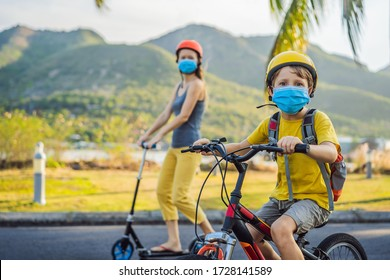 Active school kid boy and his mom in medical mask and safety helmet riding a bike with backpack on sunny day. Happy child biking on way to school. You need to go to school in a mask because of the