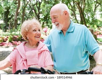 Active senio couple ride their bicycles through a park.
