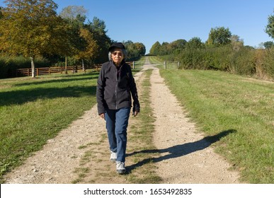 Active senior citizen, an Indian woman's daily fitness regime, walking outdoors as part of a healthy lifestyle, UK