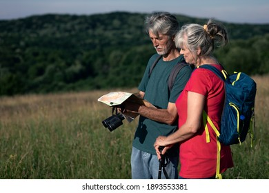 Active senior couple with backpacks hiking in nature .