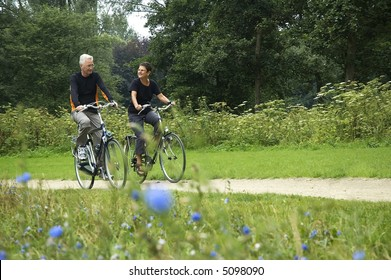 Active senior couple biking in the park, enjoying their retirement.