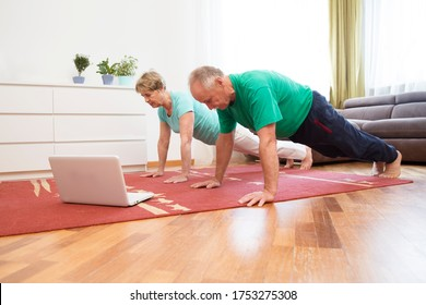 active senior couple is doing fitness training  in living room at home with laptop.  Remote Workouts.  home-based gym. home fitness, activewear.