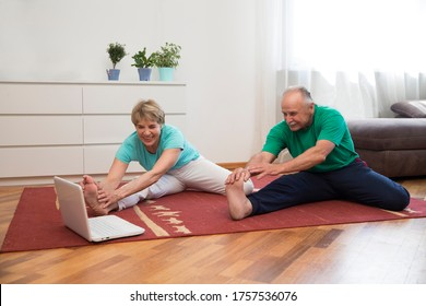 active senior couple doing stretching exercise and watching online workout tutorials on the laptop in living room at home.  home fitness, activewear.