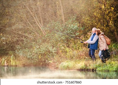 Active senior couple fishing at the lake. A woman and a man in a beautiful autumn nature in the early morning.