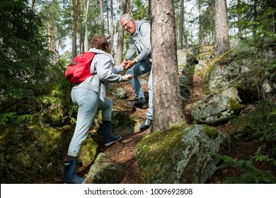 Active senior couple hiking on the forest rock. Mature man helping woman climbing up. Happily smiling. Scenic view green wood. Healthy lifestyle. Finland.