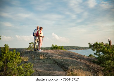 Active senior couple hiking on the top of rock, exploring. Mature man and woman Happily smiling. Nordic walking, trekking. Scenic view of gulf and sea. Healthy lifestyle. Finland.