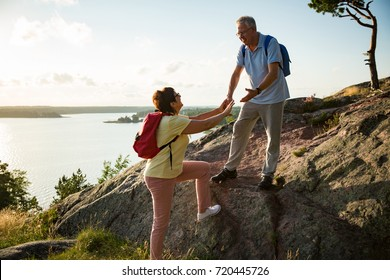 Active senior couple hiking on the top of rock. Mature man helping woman climbing up. Happily smiling. Scenic view of gulf and sea. Healthy lifestyle. Finland.