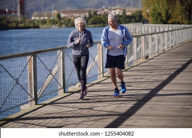 Active senior couple jogging together on bridge
