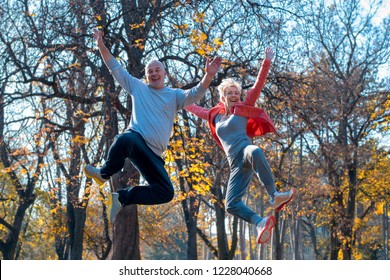 Active senior couple jumping and exercising outside in park