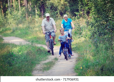 active senior couple with kids riding bikes in nature