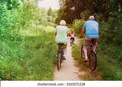 active senior couple with little granddaughter riding bikes in nature