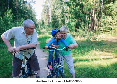 active senior couple with little granddaughter on bikes in nature