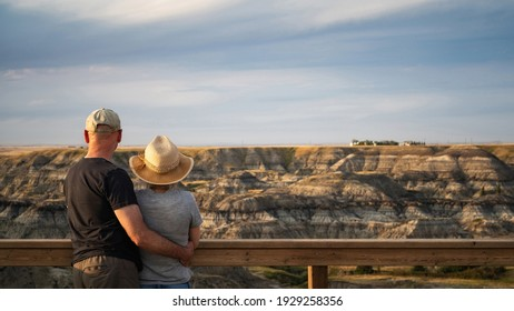 Active senior couple looking at view at Horseshoe Canyon near Drumheller in Alberta, Canada.