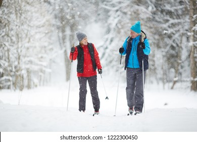 Active senior couple on skis moving down snowdrift in snowfall during training in winter forest