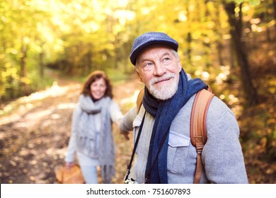 Active senior couple on a walk in a beautiful autumn nature.