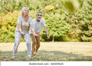 Active senior couple playing with flying disc with vitality in summer