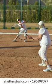 Active senior couple playing tennis outdoors together