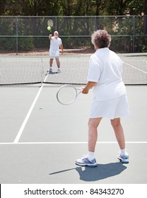 Active senior couple playing tennis together on an outdoor court
