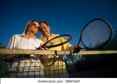 Active senior couple is posing on the tennis court with tennis racket in hand. Outdoor, sunlight.