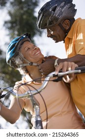Active senior couple preparing to cycle in park, man adjusting woman's cycling helmet strap, smiling, close-up, low angle view (tilt)