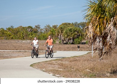 Active senior couple riding their bicycles on a beautiful sunny day.