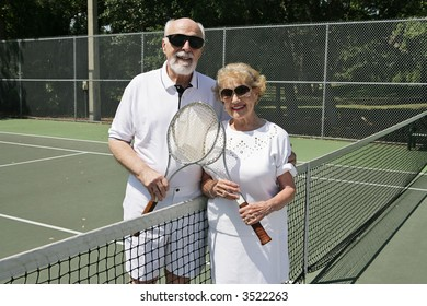 An active senior couple in sunglasses getting ready to play tennis.