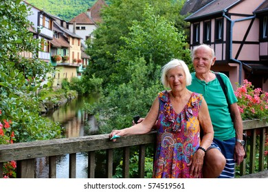Active senior couple traveling in France. Elderly people visiting Alsace region, walking on the streets of Kaysersberg town. Man and woman enjoying french cities, villages and countryside