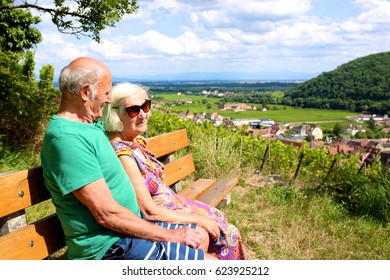 Active senior couple traveling in France. Elderly people visiting Alsace region, enjoying view on vineyards from top of Kaysersberg. Man and woman enjoying french cities, villages and countryside.