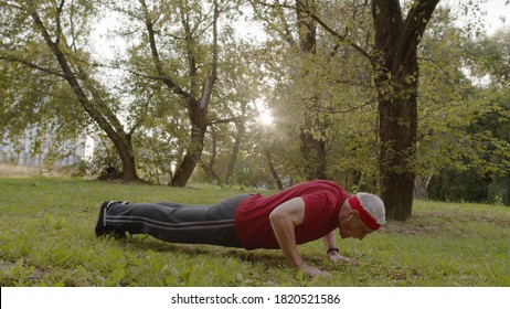 Active senior elderly 80 years old caucasian man doing morning push-ups physical exercises in city park. Grandfather training fitness workout. Healthy lifestyle in old age
