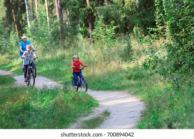 active senior with grandkids riding bikes in nature