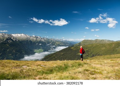 active senior hiker resting in austrian alps and looking on high mountain glacier view